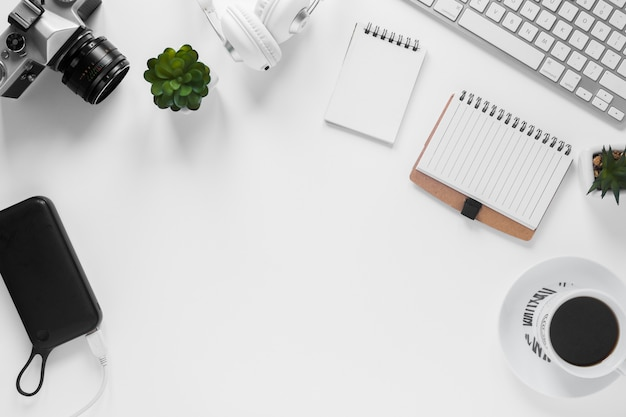 Camera; power bank; cactus plant; dagboek; theekop en toetsenbord op wit bureau