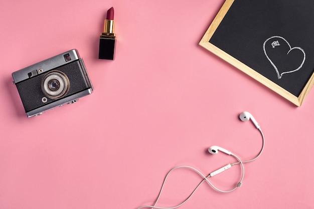 Camera, rode lippenstift, witte oortelefoons en een klein bord