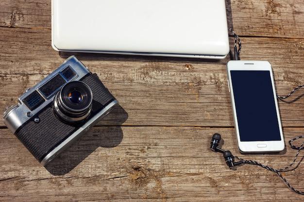 Camera telefoon en laptop zijn op een houten tafel