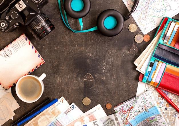 Camera, toeristische kaarten, paspoort, kopje koffie, koptelefoon, portemonnee met creditcards, eurobankbiljetten en munten op het zwarte bureau.