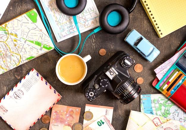 Camera, toeristische kaarten, paspoort, speelgoedauto, koffie, koptelefoon, portemonnee met creditcards, eurobankbiljetten en -munten op een zwart bureau. reis achtergrond.