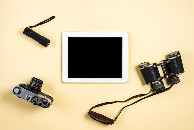 Camera; zaklamp; verrekijker en digitale tablet op beige achtergrond