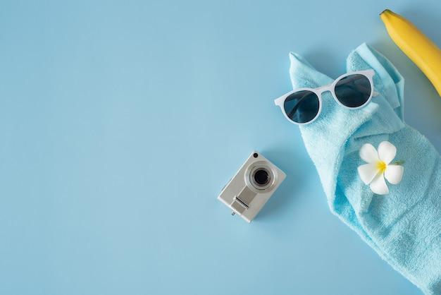 Camerabril en handdoek op een blauwe achtergrond