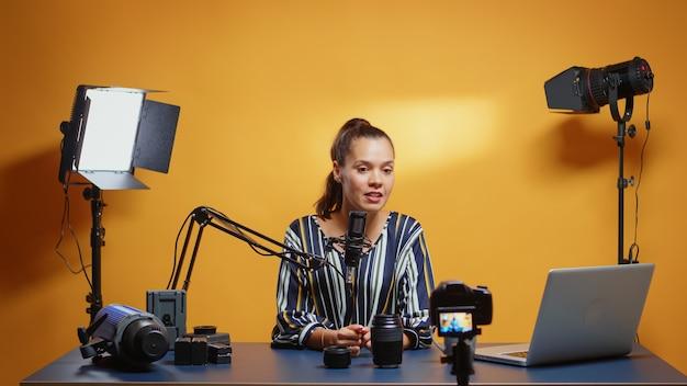 Cameralensvergelijking van online vlogger in haar professionele studio. contentmaker nieuwe media ster influencer op sociale media pratende video-fotoapparatuur voor online internetwebshow