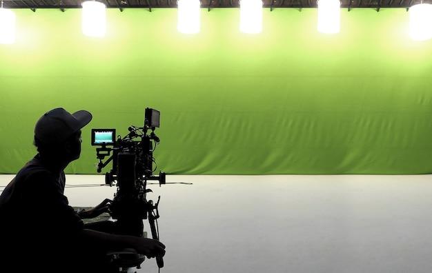 Cameraman en gereedschap en witte vloer en studio met groot groen scherm.