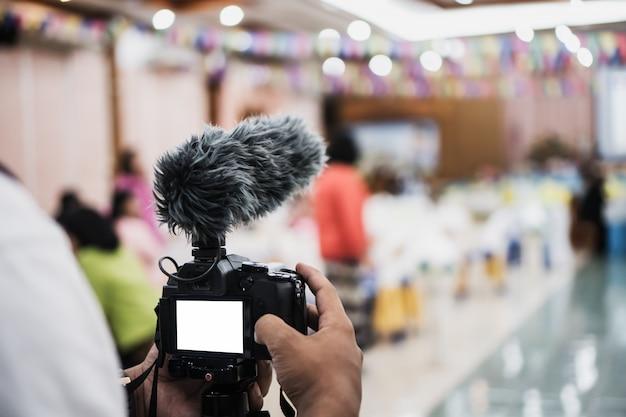 Cameraman video of professionele digitale spiegel minder op statief voor camera-opname met microfoon