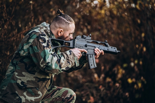 Camouflage soldaat met geweer en geschilderd gezicht airsoft buiten spelen in het bos