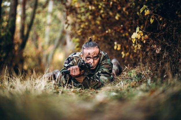 Camouflage soldaat met geweer en geschilderd gezicht liggend in het gras gericht op het geweer.