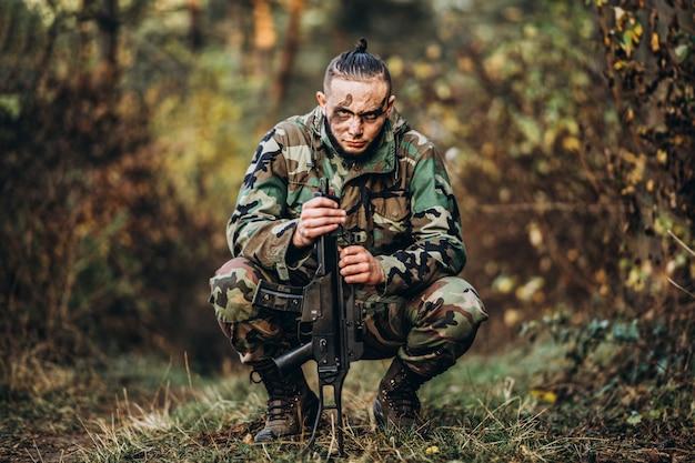 Camouflagemilitair met geweer en geschilderde gezichtzitting in het gras.