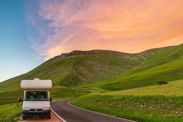 Camper aan de kant van de weg in prachtig landschap. dramatische hemel bij zonsondergang, schilderachtige wolken boven unieke hooglanden en heuvelruggen in italië, alternatief vanlife-vakantieconcept.