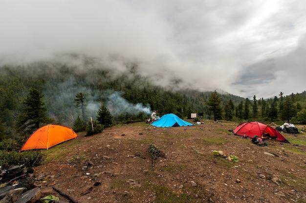 Camping in de bergen begroeid met bos. toerist bij de blauwe tent. dichte mist rond en wolken. horizontaal.