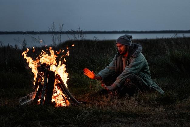 Camping man zit bij het vuur 's nachts tegen de hemel. reizen, toerisme, kamperen.