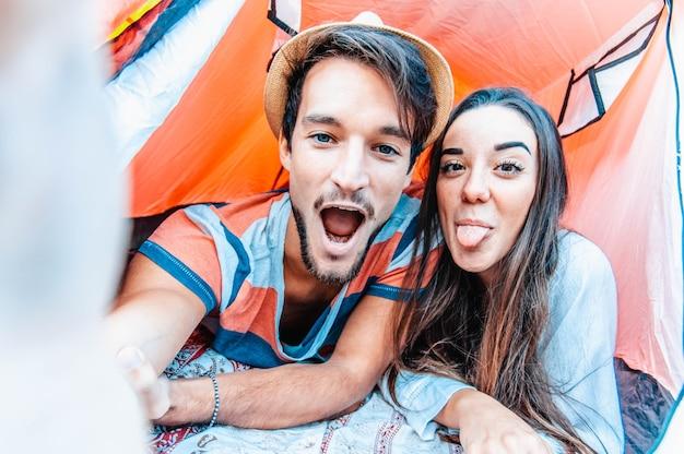 Camping paar in tent selfie te nemen. gelukkige vrienden die samen plezier hebben.