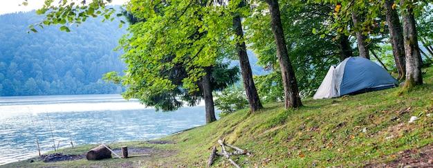 Camping tent aan de oever van een panorama van het meer