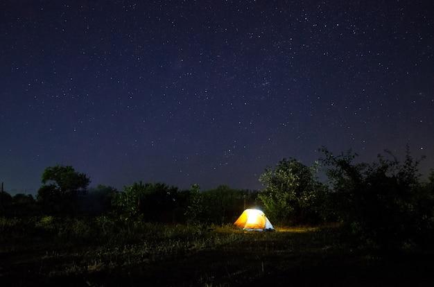 Camping tent onder prachtige nachtelijke hemel vol sterren. sterrenhemel boven verlichte toeristische tent.