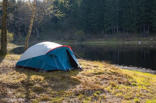 Camping tent opgezet in de buurt van het meer in het bos. buiten op een camping relaxen.