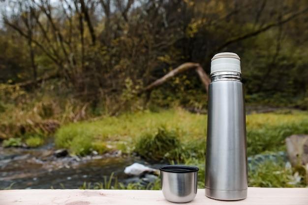 Camping vacuüm thermoskan met een mok op een bos en een beek. concept voor buitenactiviteiten, warme dranken, wandelen, reizen.