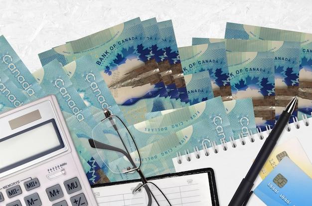 Canadese dollarsrekeningen en rekenmachine met glazen en pen