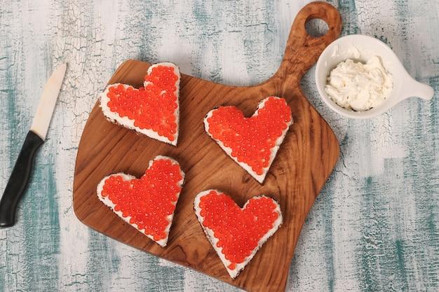 Canapé met rode kaviaar en roomkaas in de vorm van een hart voor valentijnsdag, bovenaanzicht