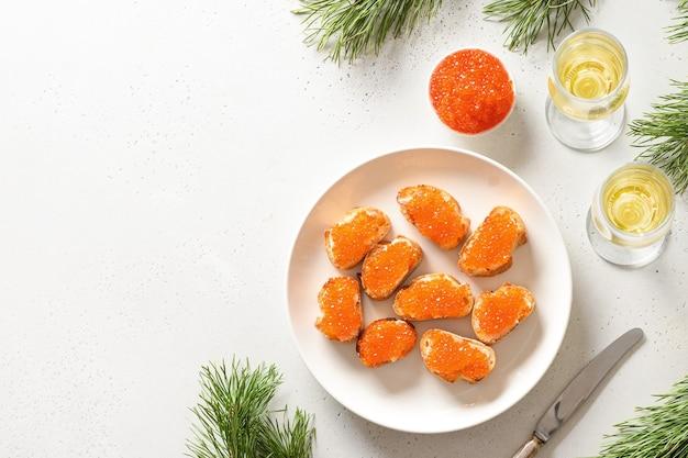Canapé met rode kaviaar geserveerd met champagne voor nieuwjaar of kerstfeest op witte tafel.