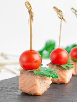 Canapeetjes met gebakken forel, kerstomaatjes en peterselie. op een donkere leisteen bord. detailopname. geïsoleerd. witte achtergrond