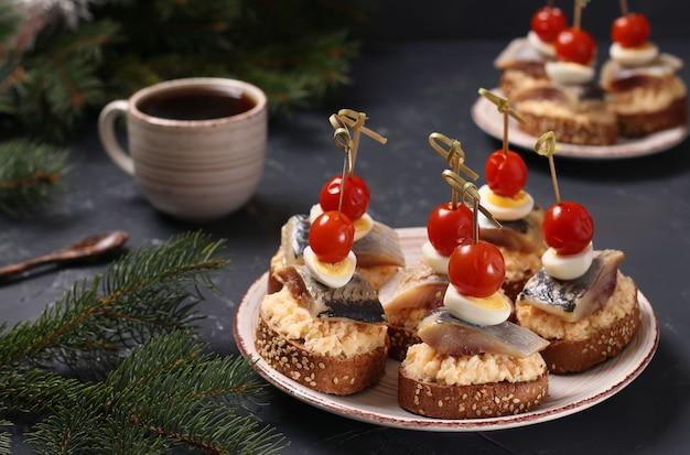 Canapeetjes met gezouten haring, kaas, kwarteleitjes en kerstomaatjes op rogge croutons en kopje koffie op donkere tafel. horizontaal formaat. detailopname