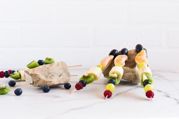 Canapeetjes van sappig fruit en bessen op stenen, zijaanzicht.