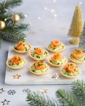 Canapes met gerookte zalm, roomkaas en avocado op lichte achtergrond met ruimte voor tekst. kerstmis en nieuwjaar vakantie achtergrond concept.