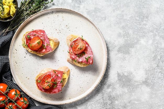 Canapes met salami salchichon, kerstomaatjes en microgreens op een stokbrood. grijze achtergrond