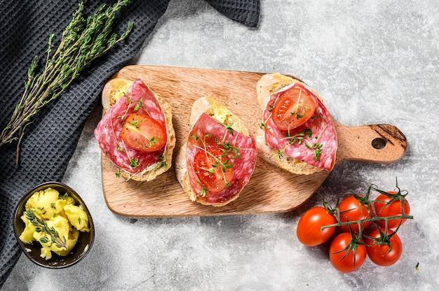Canapes met salami salchichon, kerstomaatjes en microgreens op een stokbrood
