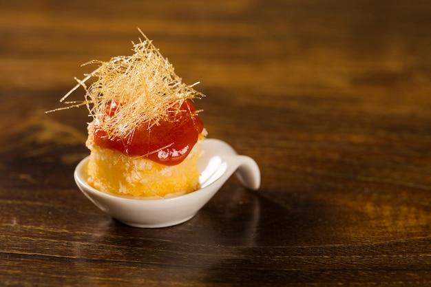 Canasta-kaasmousse met guave-gelei en romige maïsmeelcake in een lepel