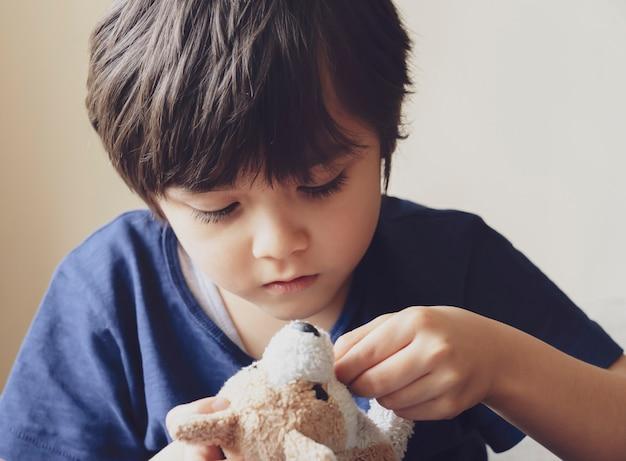 Candid korte od kleine jongen speelt met pluizige hond, soft focus adorable 6-7 jaar oude jeugd ontspannen thuis in de zomer. kid geconcentreerd spelen met zijn speelgoed.