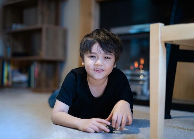 Candid shot gelukkig kind liggend op de vloer spelen met plastic speelgoed,
