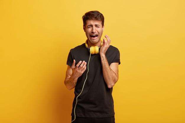 Candid shot van boos bedroefd man gebaren en huilt, heeft problemen met technologie