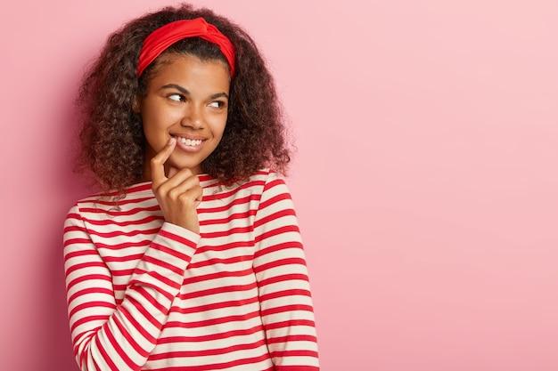 Candid shot van peinzende tiener met krullend haar poseren in gestreepte rode trui
