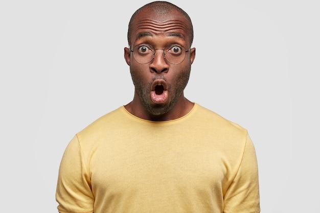 Candid shot van verbijsterd emotionele african american man in gele vrijetijdskleding