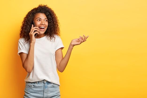Candid shot van zorgeloze jonge vrouw met krullend haar poseren met haar telefoon