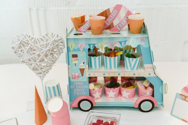 Candy bar in de vorm van een bus, versierd met roze tinten.