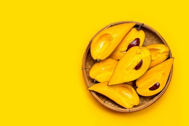 Canistelfruit in bamboemand op gele achtergrond.