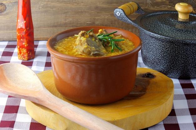 Canjiquinha een traditioneel gerecht uit de braziliaanse keuken gemaakt met varkensribbetjes en gemalen maïs, in een keramische kom op een rustieke houten tafel. close up bekijken