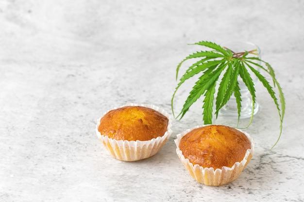 Cannabis cupcake muffins en bladeren op grijs.