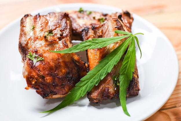 Cannabis eten met bbq varkensribbetjes gegrilde kruiden specerijen geserveerd geroosterde barbecue varkensvlees sparerib marihuana blad