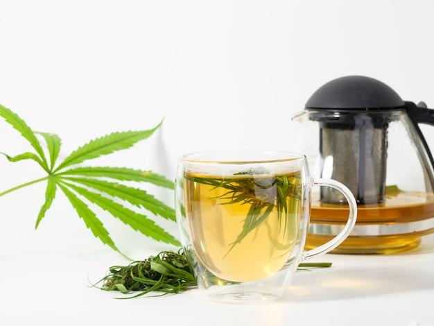 Cannabis theekop met marihuanabladeren en bloem in glazen beker, cbd-olie bruine ketel op wit
