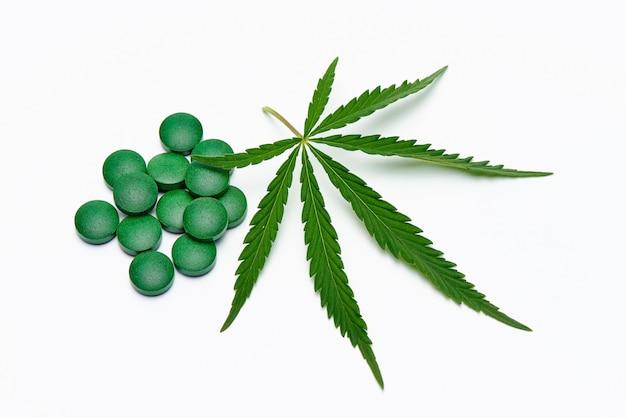 Cannabisblad en pillen op een witte ruimte.