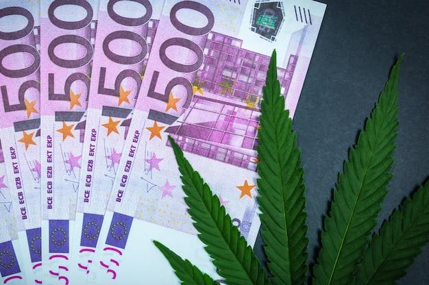 Cannabisblad op de achtergrond van bankbiljetten. drugshandel concept.
