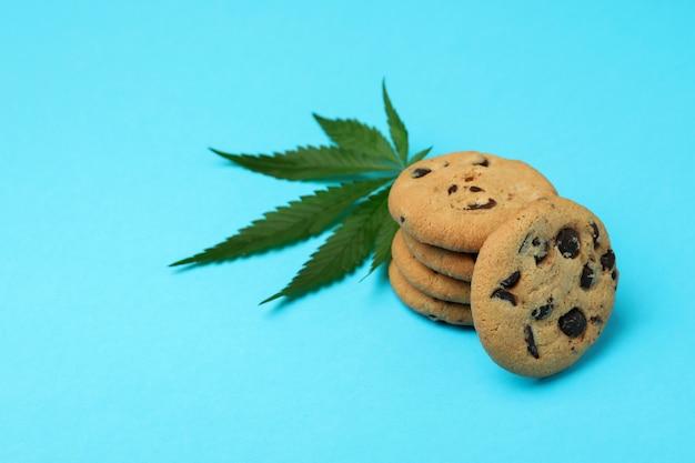 Cannabiskoekjes en blad op blauwe achtergrond