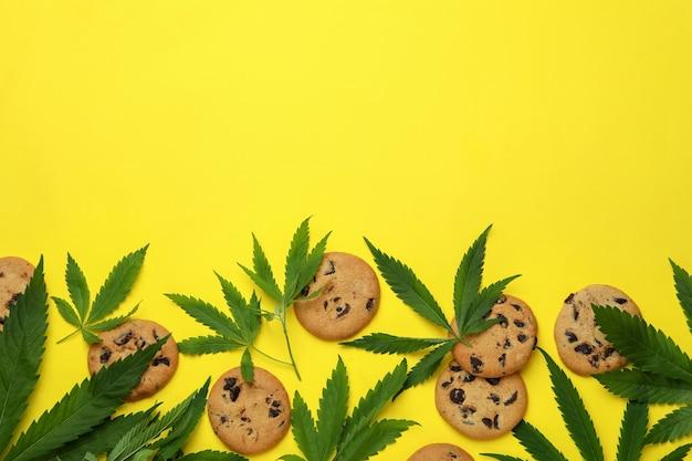 Cannabiskoekjes en bladeren op gele achtergrond