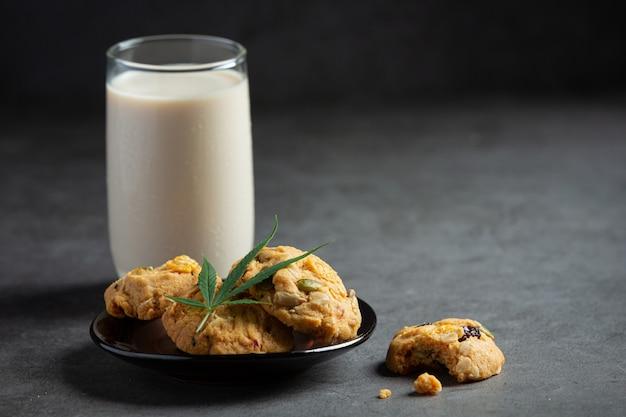 Cannabiskoekjes en cannabisblad op zwarte kom, geserveerd met een glas melk