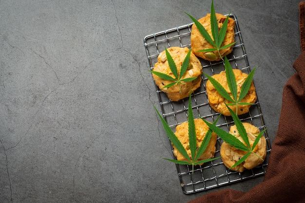 Cannabiskoekjes en cannabisbladeren op een donkere vloer