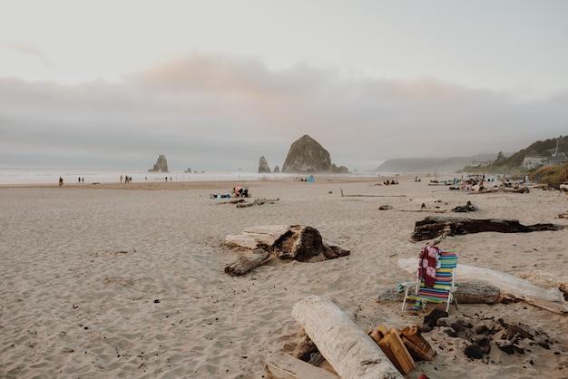 Cannon beach omringd door vakantiegangers met de haystack rock onder een bewolkte hemel